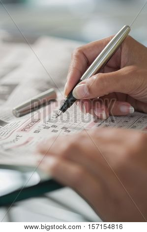 Solving a crossword puzzle close-up. Hand of a woman doing a crossword
