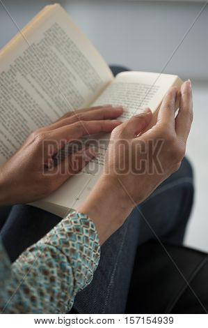 Young woman reading a book on a couch close-up on home interior background