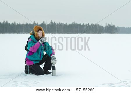 Winter sitting on haunches hiker with metal drink flask is resting at snowy landscape background