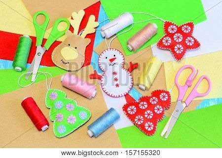 Easy Christmas tree ornaments crafts. Felt Christmas tree, star, snowman, deer diy, colored thread, felt sheets, needles, scissors. Homemade Christmas tree ornaments idea. Winter kids craft background