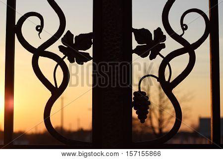 Detail iron-shod fence in the sunset. Orange sunset