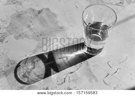 Glass of water with shadow on the white metallic table