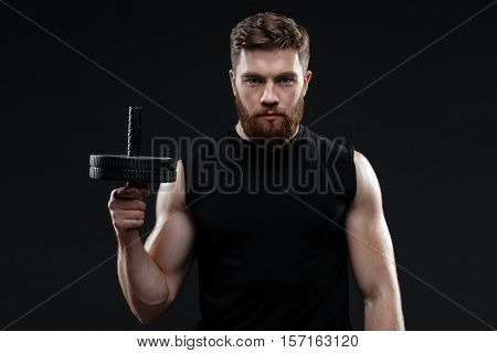 Athletic man with wheel. front view. holding wheel in hand. isolated dark background