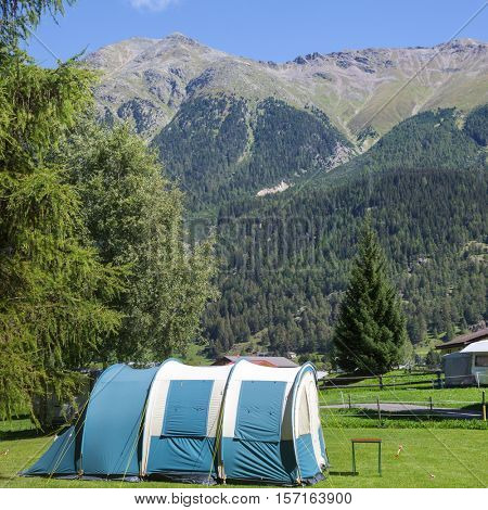 Camping tent at a campsite in Switzerland on a sunny summer day with Alps in background
