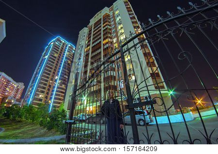 Girl In The Yard At Night. Young Blond Woman Standing Alone In Wrought Fence.