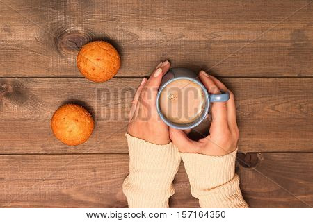 A Cup Of Cocoa In The Hands On A Wooden Background. Blue Sweater And Mini Muffins. Top View