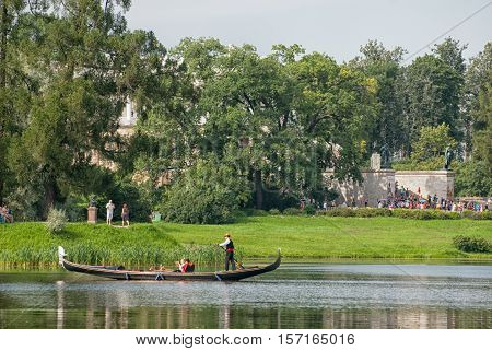 TSARSKOYE SELO, SAINT - PETERSBURG, RUSSIA JULY 25, 2016: Gondolier and people in the gondola on The Great Pond in The Catherine Park. On the background is The Cameron Gallery