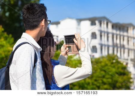 Young couple watching a multistory white villa with balcony and take pictures with the mobile phone