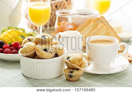 Fresh and bright continental breakfast table with coffee, muffins and fruits