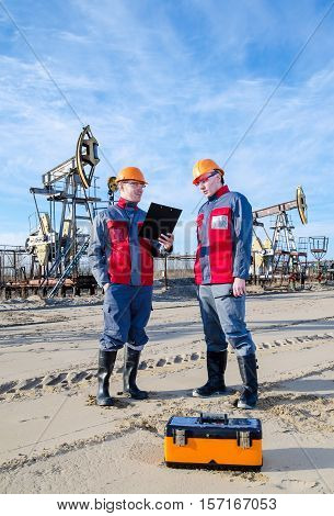 Two workers in the oilfield one holding the radio second showing papers. Pump jack and wellhead background. Oil and gas concept.