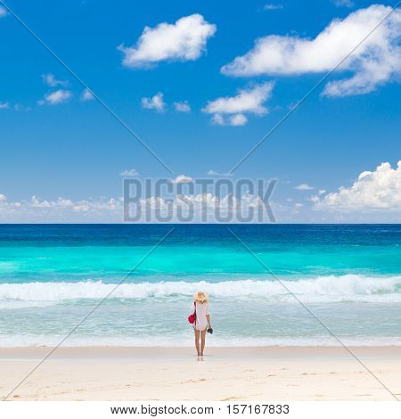 Woman wearing white tunic and beach hat, enjoying amazing view of Police Bay on Mahe Island, Seychelles. Summer vacations on picture perfect tropical beach concept.