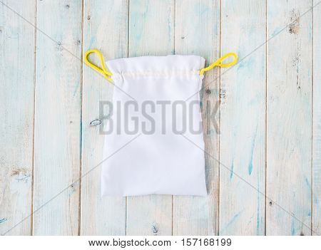 white little fabric gift sac with yellow ties on wooden table