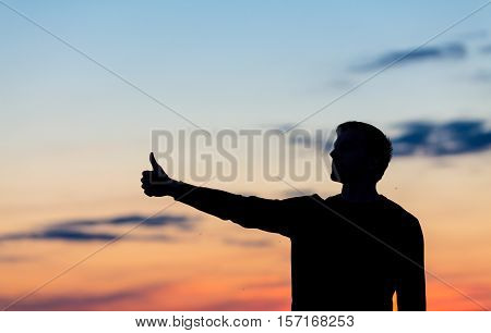 Silhouette Of Male Celebrating With Arm Up Towards The Sunrise.