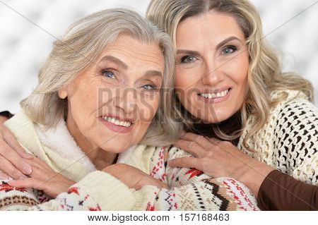 Portrait of smiling senior woman with daugther hug looking at camera