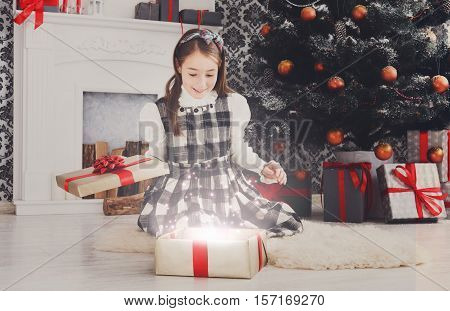 Beautiful happy excited girl unwrap magic christmas present on holiday morning in beautiful room. Female child open Xmas gift near decorated fir tree and fireplace. Winter holidays concept