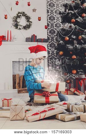 Cute happy boy in santa hat unwrap magic christmas present on holiday morning in beautiful room. Male child open Xmas gift near decorated fir tree and fireplace. Winter holidays concept