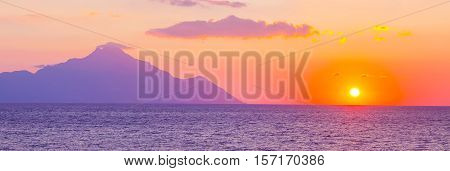 Banner background with silhouette of mount Athos at sunrise or sunset with light rays and sea panorama in Greece