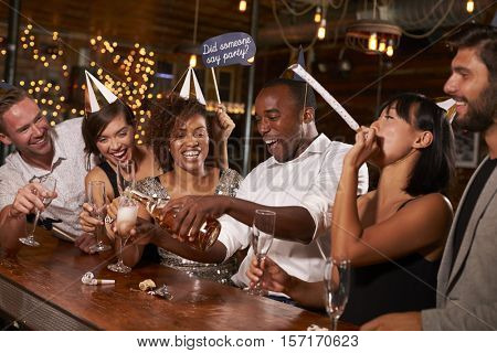 Friends pouring champagne at a New Year party at a bar