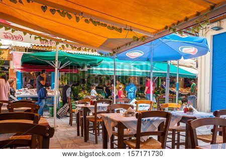 HERAKLION GREECE - OCTOBER 16 2013: The market stalls with fresh fruits and vegetables in 1866 street located behind the tables of local outdoor cafe on October 16 in Heraklion.
