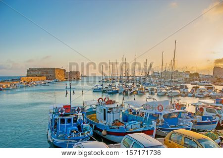 HERAKLION GREECE - OCTOBER 13 2013: The bright sunrise over the inner harbor guarded by Venetian fortress named Rocca al Mare and full of yachts and fishing boats on October 13 in Heraklion.