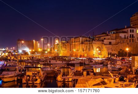 HERAKLION GREECE - OCTOBER 16 2013: The bright lights in old harbor full of fishing boats and yachts one of the best places for romantic evening walks on October 16 in Heraklion.