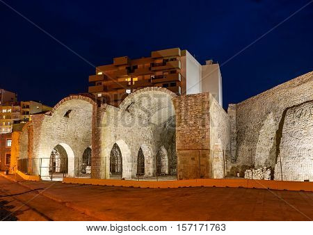 The evening walk in port of Heraklion with the view on ruins of Venetian warehouses Crete Greece.