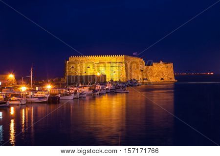 The Venetian fortress of Castello a Mare gets golden reflection in dark waters at night Heraklion Crete Greece.