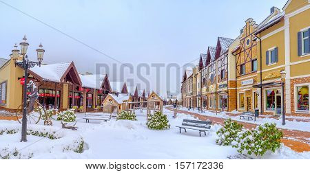KIEV UKRAINE - NOVEMBER 11 2016: The green bushes are covered with snow in park of Dutch style shopping neighborhood on November 11 in Kiev.
