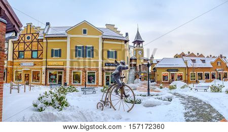 KIEV UKRAINE - NOVEMBER 11 2016: The bronze man on the vintage cycle decorates the Dutch Revival neighborhood with stepped gable houses and the tall clock tower on November 11 in Kiev.
