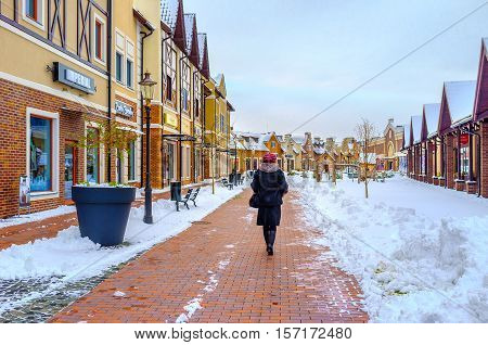 KIEV UKRAINE - NOVEMBER 11 2016: The walk along the gambrel houses of Dutch style outlet city covered with snow on November 11 in Kiev.