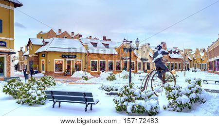 KIEV UKRAINE - NOVEMBER 11 2016: The winter in Dutch Revival style shopping city with roofs park benches and streets covered with fluffy snow on November 11 in Kiev.