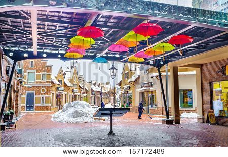 KIEV UKRAINE - NOVEMBER 11 2016: The colorful umbrellas in covered gallery of Dutch style shopping city remind about warm days on November 11 in Kiev.