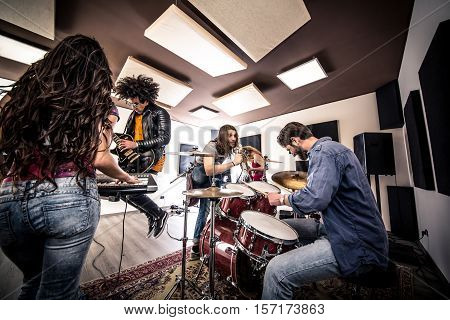 Rock band in action. Singing and recording in the studio