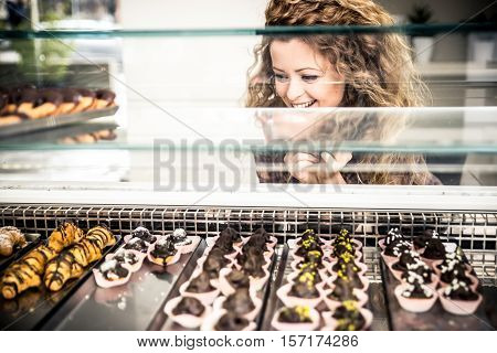 Woman watching pastries from a window. Concep about food