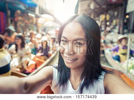 Thai woman at the floating market taking selfie with camera