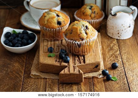 Freshly baked blueberry muffins in a rustic setting with milk and coffee on the table