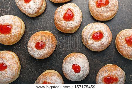 Tasty donuts with jam on dark table. Hanukkah celebration concept