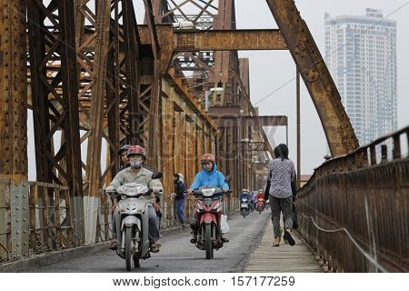 HANOI VIETNAM October 31 2016 : Long Bien bridge is a historic cantilever bridge across the Red River in Hanoi used by trains mopeds bicycles and pedestrians.