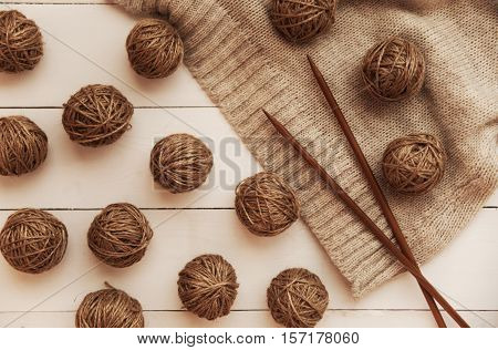 wooden white table lying knitting needles and yarn in balls