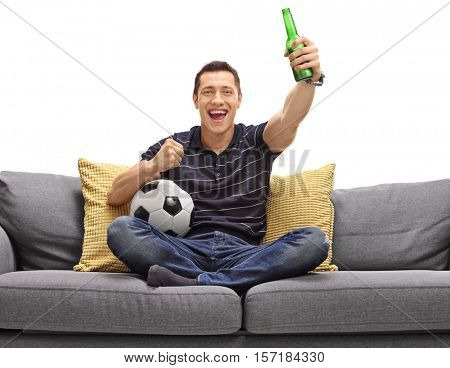 Excited guy sitting on a couch having a beer and watching football isolated on white background