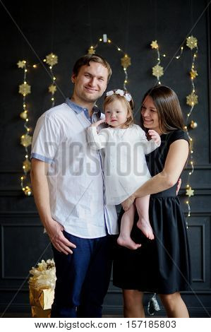 Family with little daughter is photographed in day of a holiday. Room is festively decorated. Baby is dressed in a white dress on the head of her a wreath. Girlie is capricious. Parents smile.