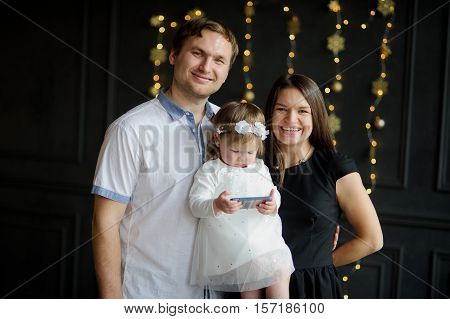Young family with kid is photographed. Chubby ruddy girl is elegantly dressed. She without coming off looks at smartphone screen. Parents smiling look in camera. Dark wall is decorated with garlands.