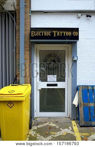Bracknell,England - November 17, 2016: Entrance door and sign for the Electric Tattoo Co, with a yellow bio hazard collection bin outside in one of the back streets of Bracknell, England