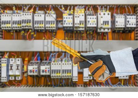 Hand In Glove Holding Screwdriver With Control Panel Cabinet