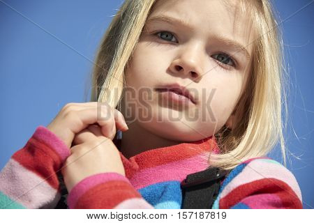 Portrait of a little child blond girl in winter sunny day against blue sky background. Girl combing and playing with her hair