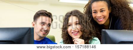 To girls and man having classes in computer room. Looking together on computer screen