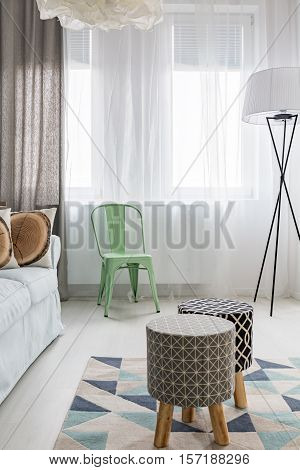 Light room with upholstered stools pattern carpet floor lamp