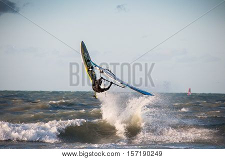 a windsurfer jumping the waves at sea