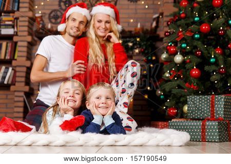 Family in sleepwear in Christmas fireplace with garlands