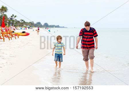 Adorable active little kid boy and his father having fun on Naples beach, Florida. Happy cute child and dad, young man collecting shells.